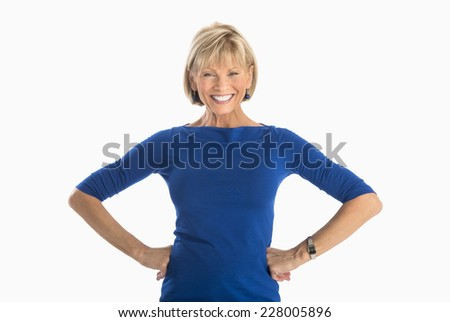 Portrait of happy mature businesswoman with hands on hip standing over white background - stock photo