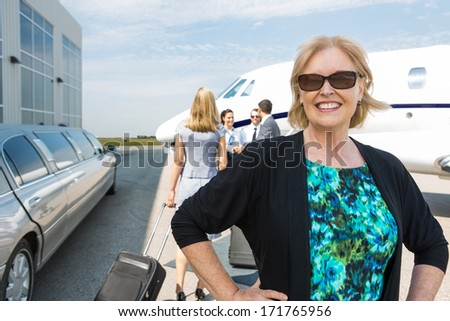 Portrait of happy mature businesswoman with limousine and private jet in background - stock photo