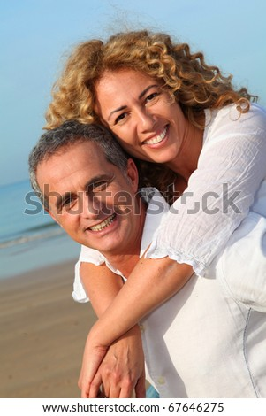 Portrait of happy mature couple at the beach - stock photo