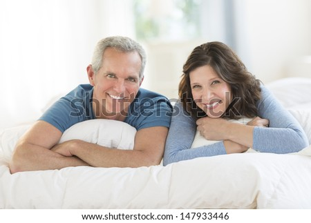 Portrait of happy mature couple lying together in bed at home