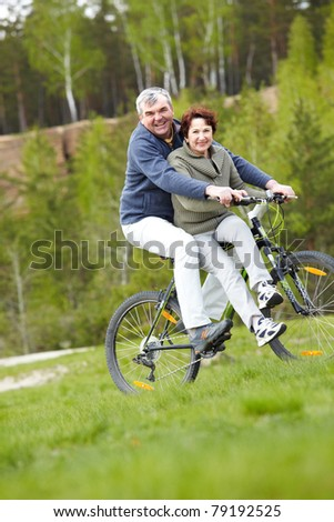 Portrait of happy mature couple on bicycle outdoors - stock photo