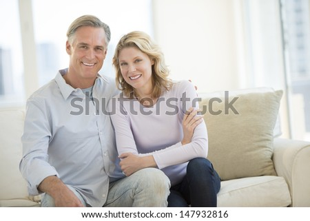 Portrait of happy mature couple sitting on sofa in living room - stock photo