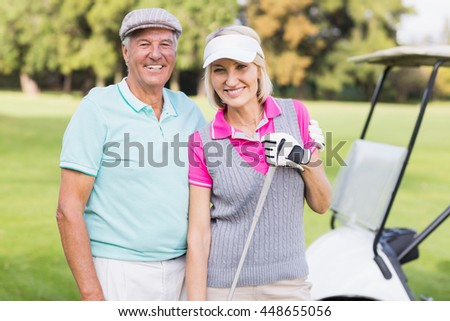Portrait of happy mature couple standing at golf course - stock photo