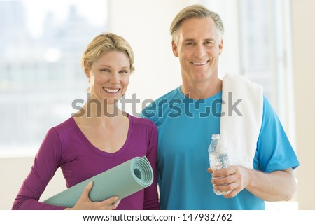Portrait of happy mature couple with exercise mat, water bottle and towel in health club - stock photo