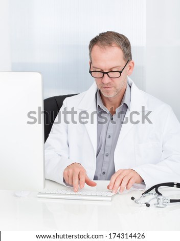 Portrait Of Happy Mature Doctor Using Computer In Clinic