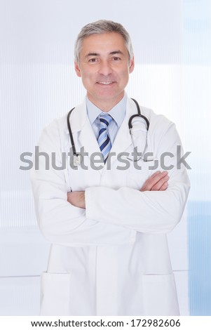 Portrait Of Happy Mature Doctor With Stethoscope - stock photo