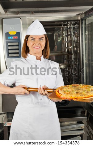 Portrait of happy mature female chef presenting pizza at commercial kitchen - stock photo