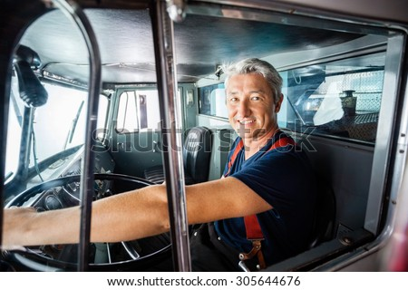 Portrait of happy mature fireman driving firetruck at station - stock photo