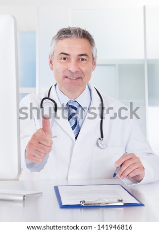 Portrait Of Happy Mature Male Doctor Showing Thumbs Up Sign - stock photo