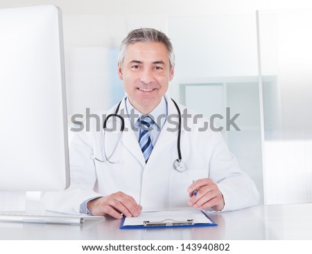 Portrait Of Happy Mature Male Doctor Working At Desk - stock photo