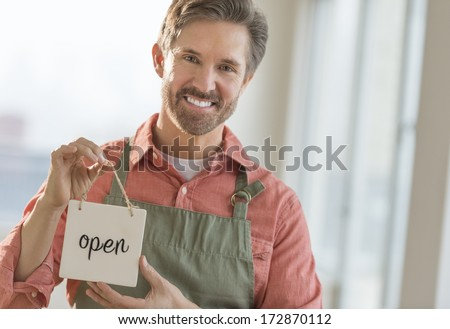 Portrait of happy mature male owner holding open signboard - stock photo