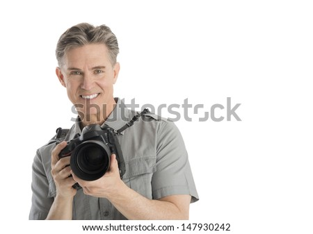 Portrait of happy mature male photographer with camera and umbrella lights isolated over white background - stock photo