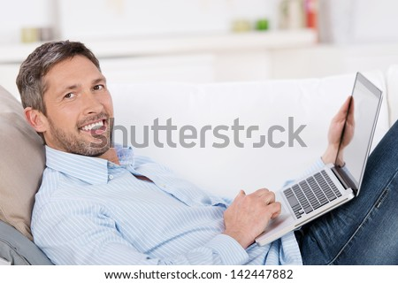 Portrait of happy mature man holding laptop while lying on sofa in house - stock photo