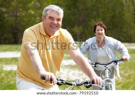 Portrait of happy mature man on bicycle with senior woman on background