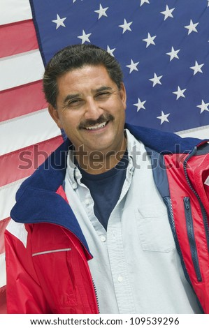 Portrait of happy mature man standing in front of an American flag