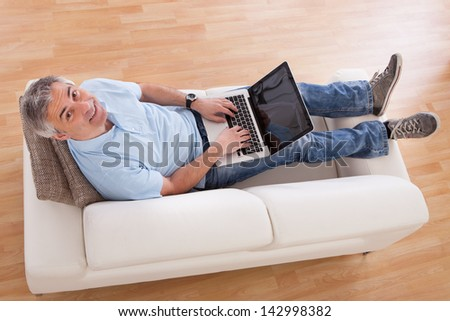 Portrait Of Happy Mature Man Using Laptop On Couch - stock photo
