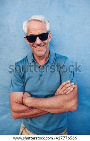 Portrait of happy mature man with sunglasses standing with his arms crossed against blue wall. Handsome mature male posing against a blue background. - stock photo