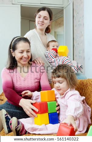 Portrait of happy mature woman and her adult daughter plays with children at home interior