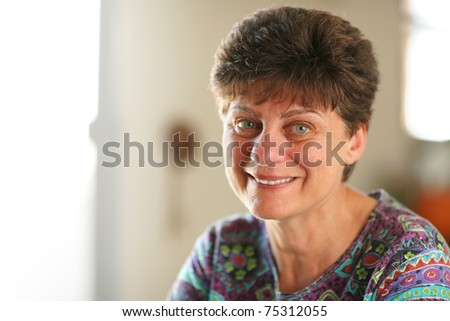 Portrait of happy mature woman at home. Closeup, shallow DOF. - stock photo