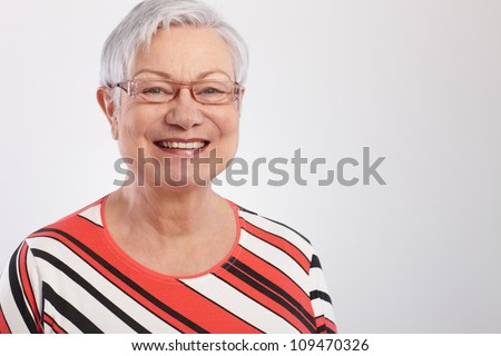 Portrait of happy mature woman in striped top. - stock photo