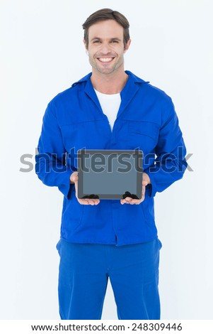 Portrait of happy mechanic holding digital tablet over white background - stock photo