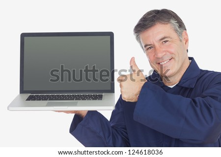 Portrait of happy mechanic with laptop showing thumbs up sign against white background - stock photo