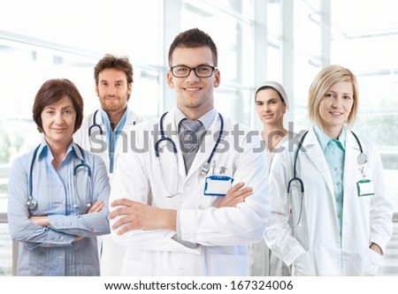 Portrait of happy medical team standing in hospital lobby.