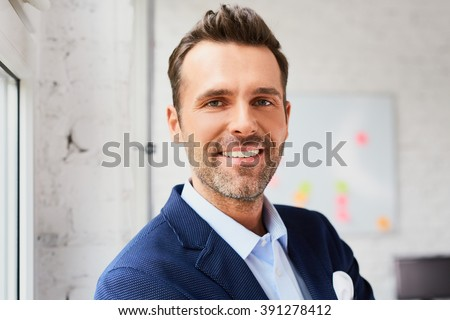 Portrait of happy mid adult businessman at office - stock photo