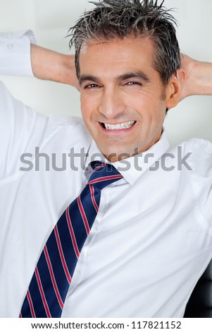 Portrait of happy mid adult businessman relaxing with hands behind head in office - stock photo