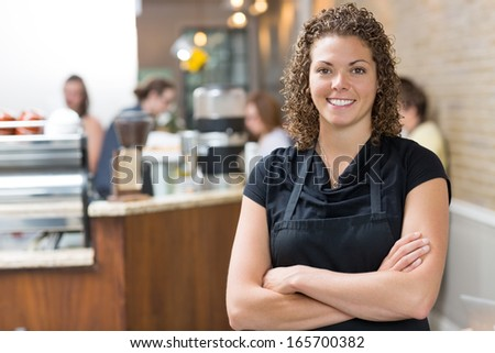 Portrait of happy mid adult female owner standing arms crossed in cafe - stock photo