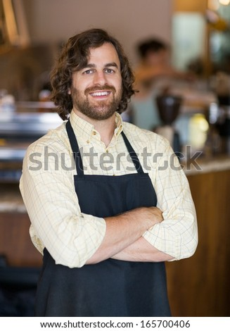 Portrait of happy mid adult male owner standing arms crossed in cafeteria - stock photo