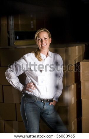 Portrait of happy mid adult woman standing in storage warehouse