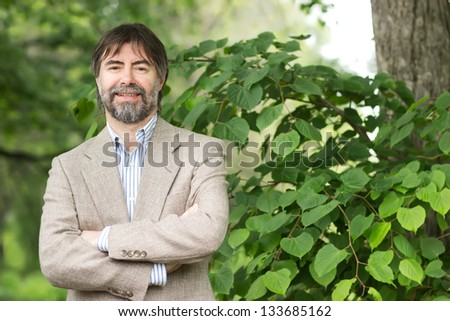 Portrait of happy middle-aged businessman looking at camera and smiling, outdoors - stock photo