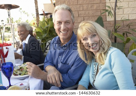 Portrait of happy middle aged couple having lunch outdoors - stock photo