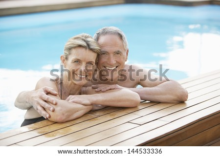 Portrait of happy middle aged couple relaxing on the edge of swimming pool - stock photo