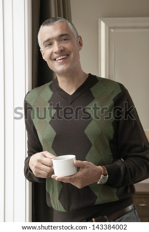 Portrait of happy middle aged man holding coffee cup at doorway