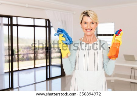 portrait of happy middle aged woman holding cleaning products at home - stock photo