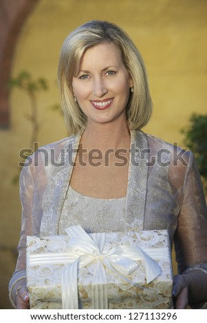 Portrait of happy middle aged woman holding gift box - stock photo