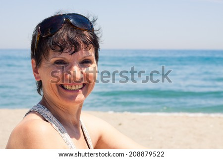Portrait of happy middle aged woman relaxing on the beach in Spain. - stock photo