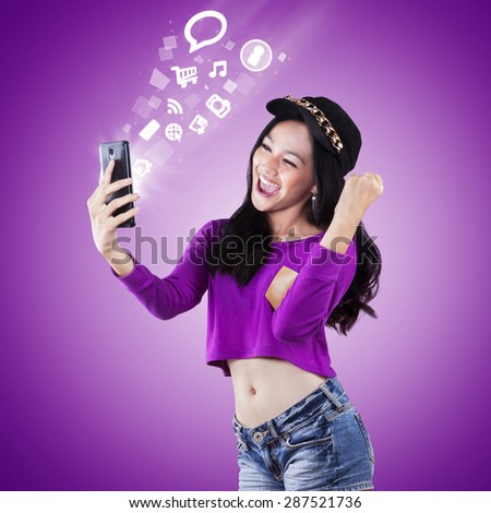 Portrait of happy modern teenage girl using smartphone to access entertainment - stock photo