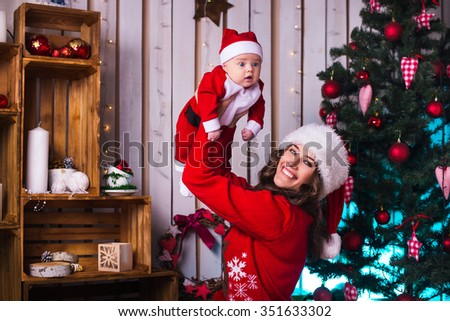 Portrait of happy mother and adorable baby in suit of Santa's little helper - stock photo