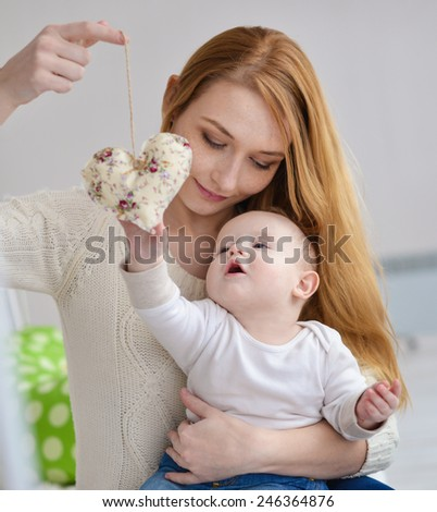 Portrait of happy mother and baby, at home - stock photo