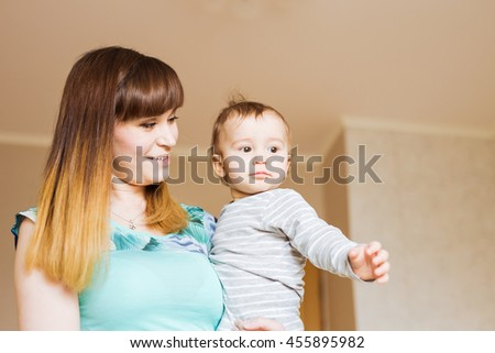 Portrait of happy mother and baby at home - stock photo