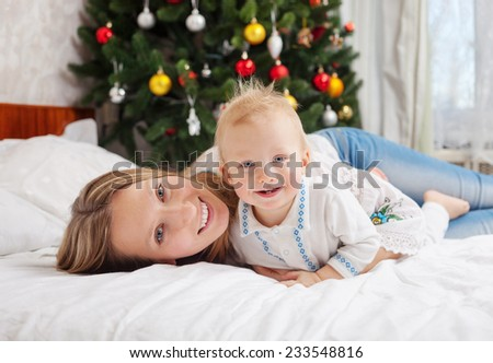 Portrait of happy mother and baby boy on bed at home with decorated Christmas tree in background - stock photo