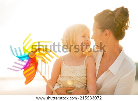 Portrait of happy mother and baby girl holding colorful windmill toy on the beach in the evening - stock photo
