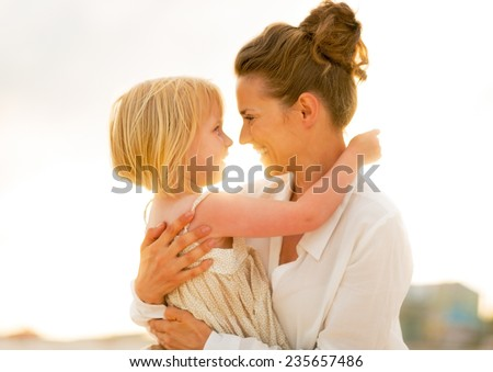 Portrait of happy mother and baby girl hugging on beach at the evening - stock photo
