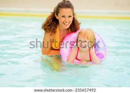 Portrait of happy mother and baby girl with swim ring swimming in pool - stock photo