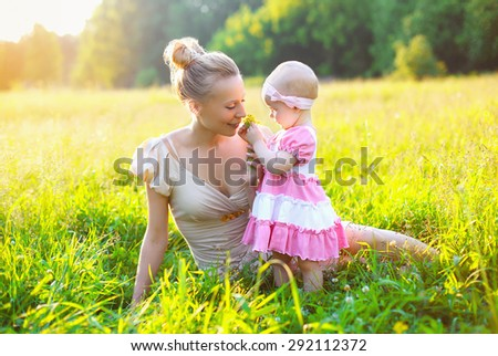 Portrait of happy mother and baby little daughter wearing a dress in sunny summer day together on the grass meadow - stock photo