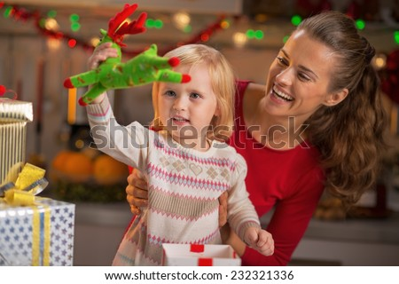 Portrait of happy mother and baby playing in christmas decorated kitchen - stock photo