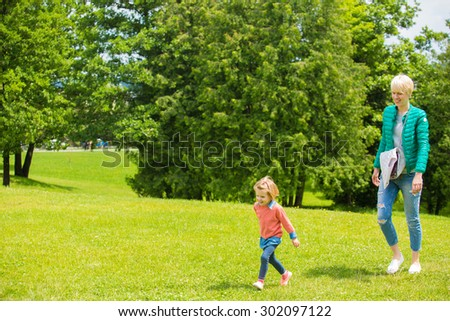 Portrait of happy mother and baby playing outdoors - stock photo